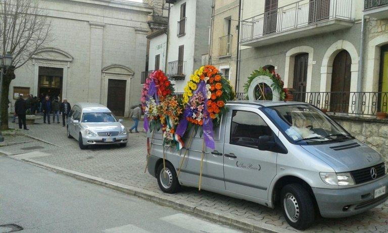 un furgone con delle corone di  fiori e dietro un carro funebre