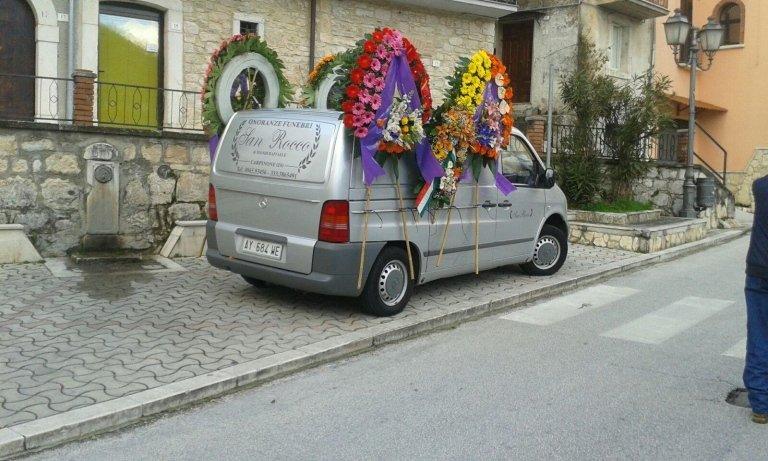 un furgone grigio con delle corone di fiori colorati
