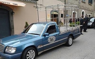 un carro funebre azzurro con una struttura in metallo sul retro