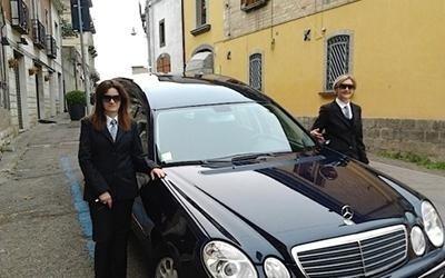 due persone vicino a un carro funebre