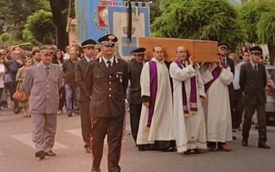 dei comandanti militari e dei vescovi che reggono una bara durante una marcia funebre