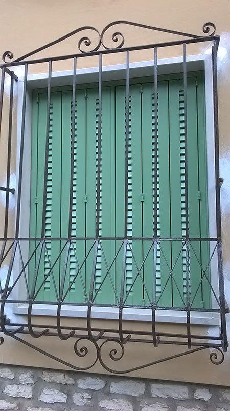 una griglia a una finestra con una persiana verde