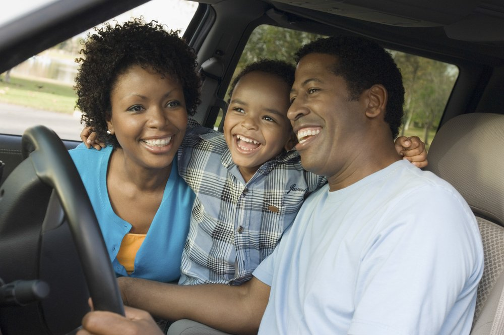 Happy family in minivan - Reliable Car Rental