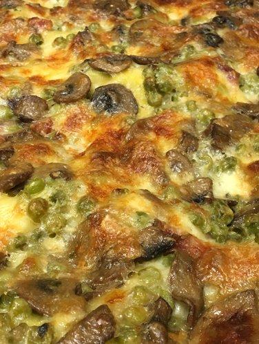 primo piano di una pizza con funghi e piselli