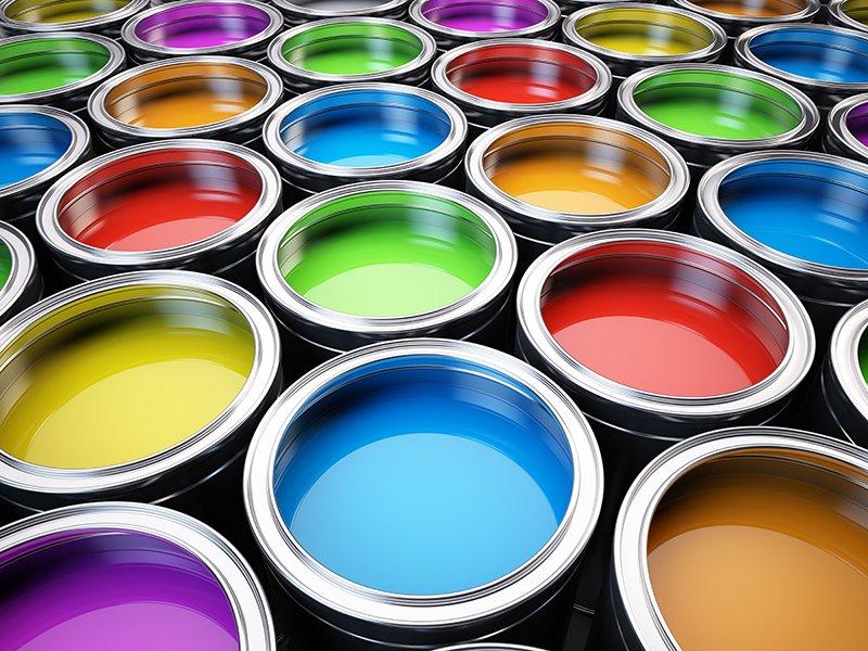 dei secchi di metallo con dentro delle vernici di diversi colori