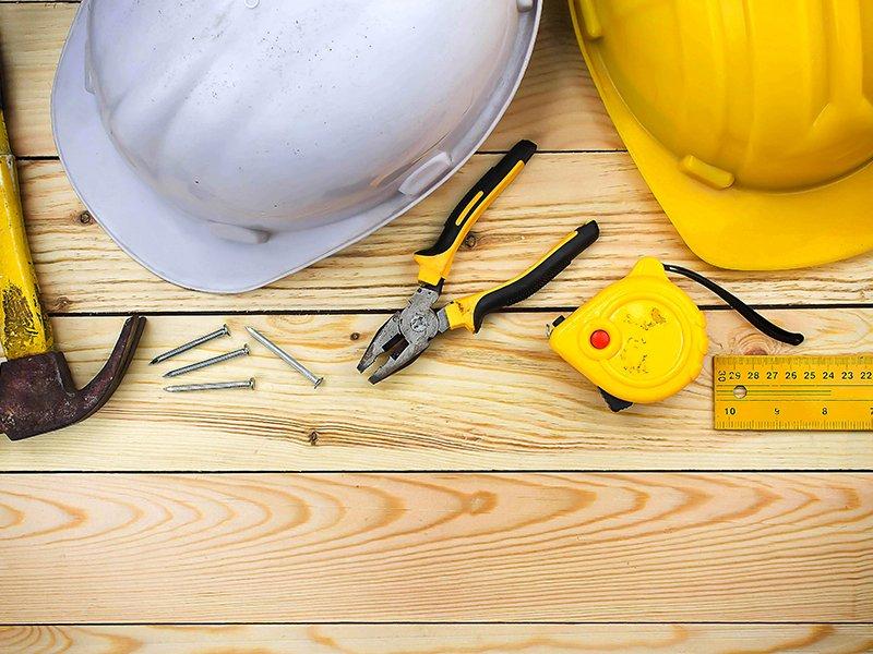 due elmetti, uno giallo e uno bianco,un martello,un cacciavite, viti pinza e un metro su un tavolo di legno