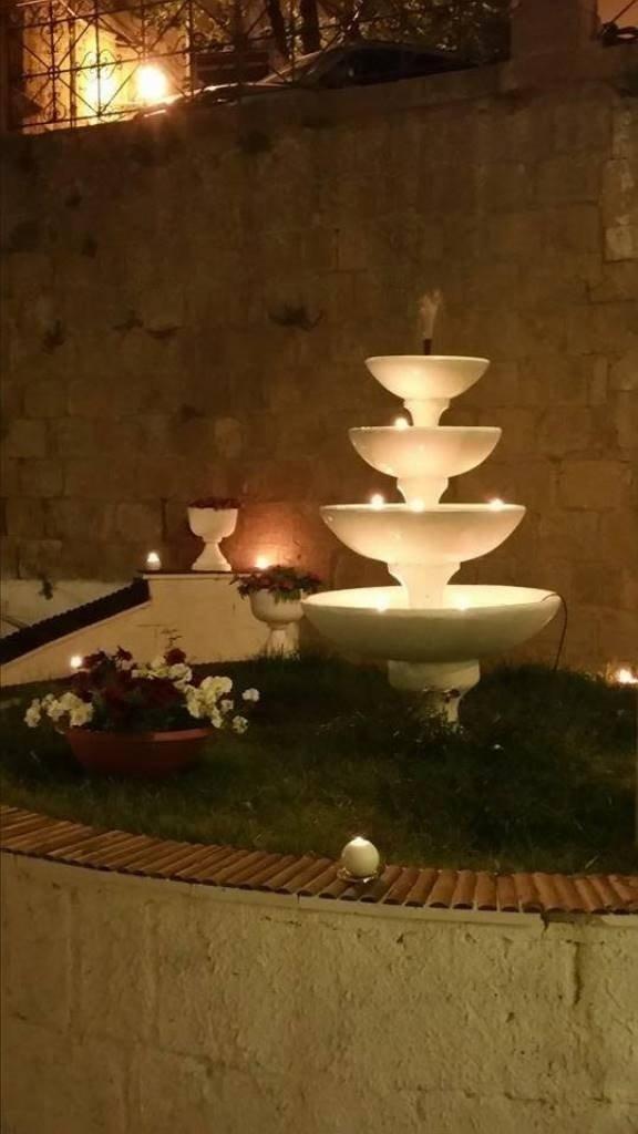 una fontana illuminata in un giardino