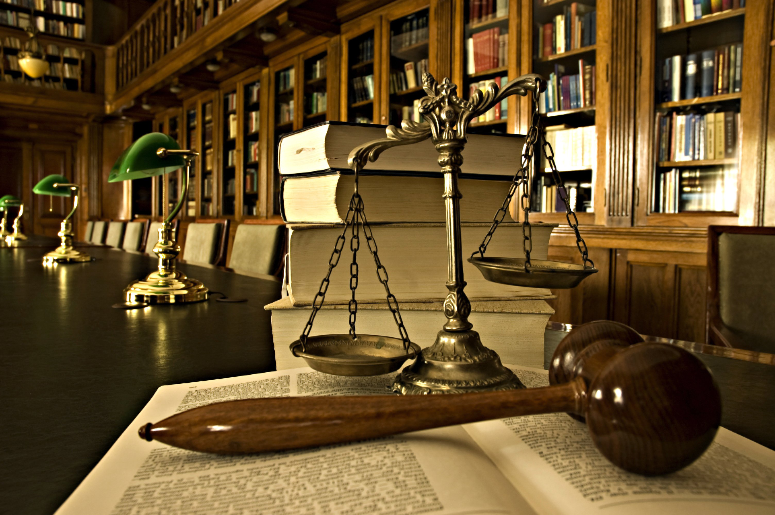 Open law books in library with gavel and scale
