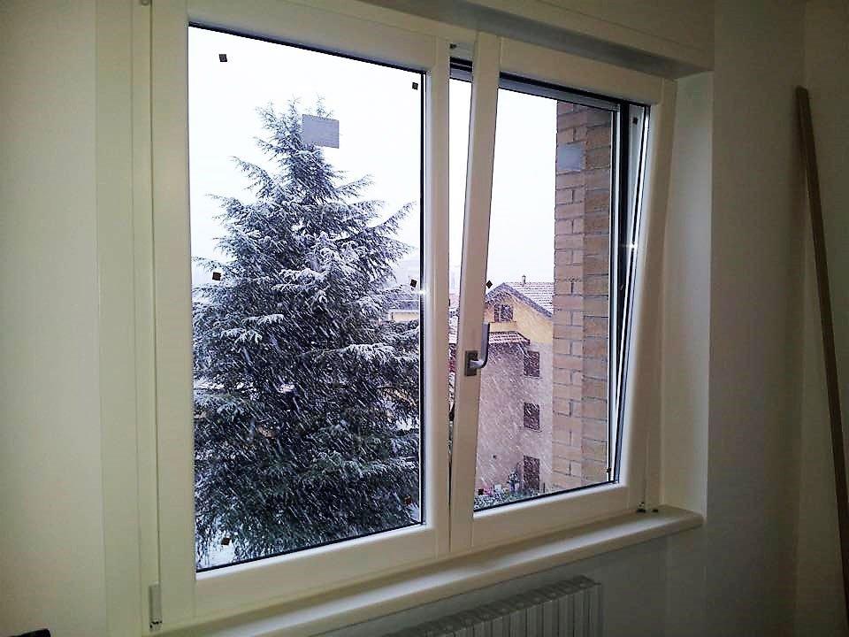 una finestra in pvc semi aperta e vista di un albero innevato all'esterno