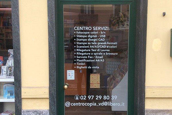 la porta d'entrata in vetro della copisteria con scritti i servizi offerti
