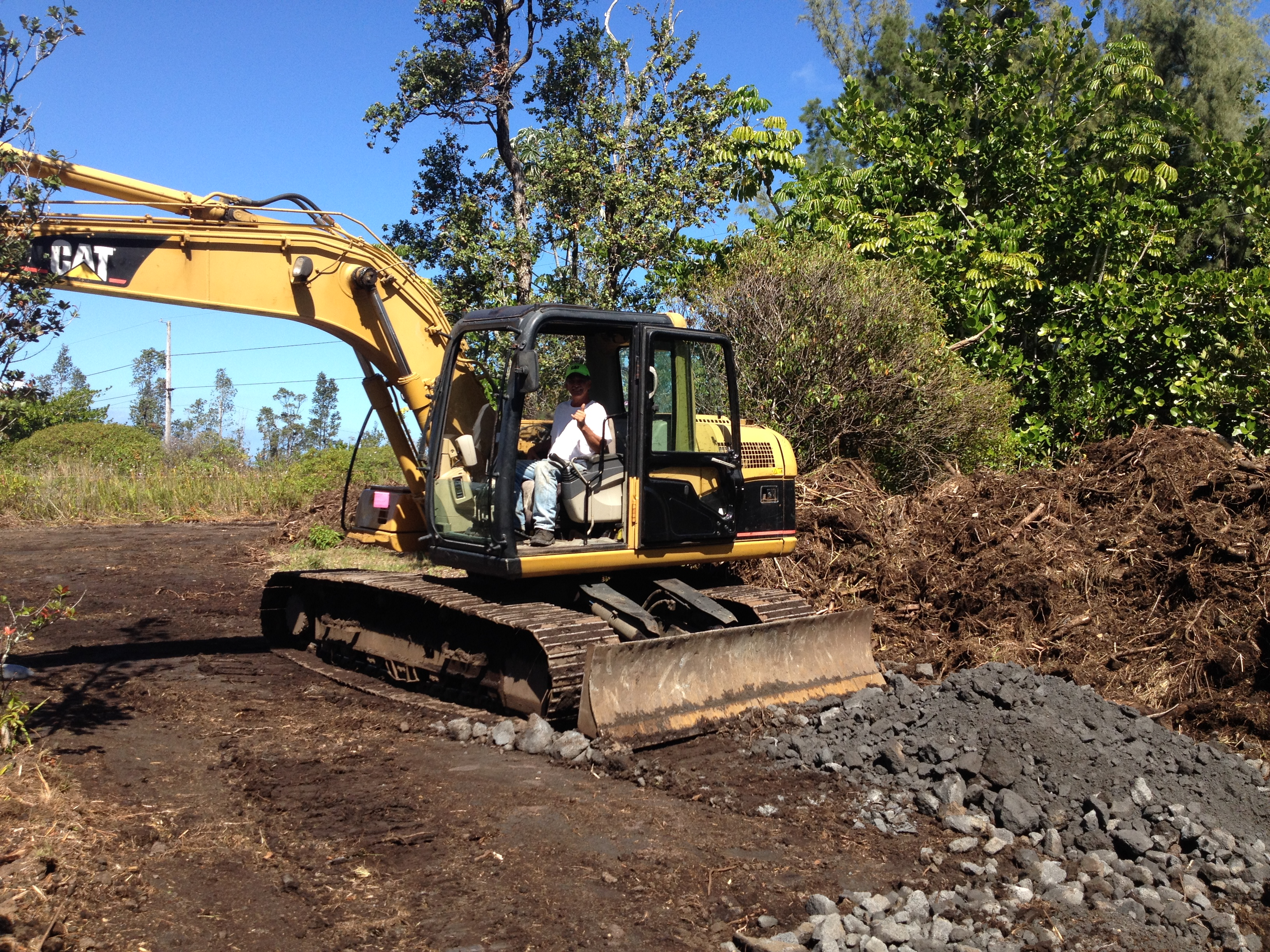 Plumbing experts using crane for septic system excavation and installation in Hilo, Hawaii