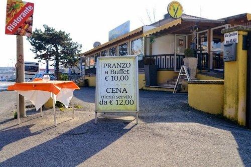 vista dall'esterno di un ristorante e un cartellone con scritto Pranzo a buffet 10 euro