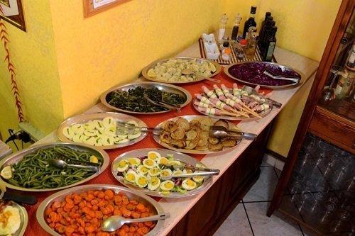 un buffet con vassoi di verdura, uova sode e grissini con prosciutto cotto