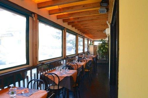 una veranda con dei tavoli apparecchiati