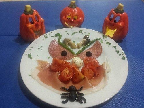 un piatto con degli affettati, pomodori e accanto delle decorazioni di halloween