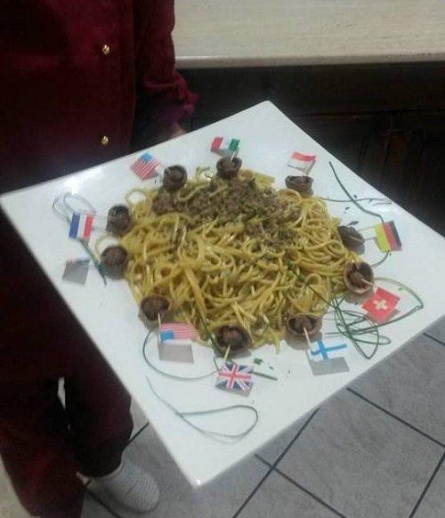 un piatto di spaghetti  e delle bandierine attorno