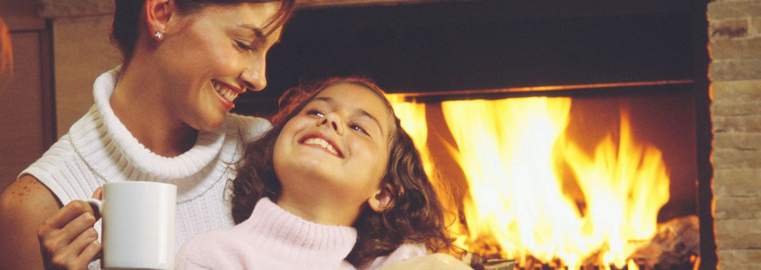 woman and girl in front of fireplace installed by heating and cooling services in Wisconsin Rapids, WI