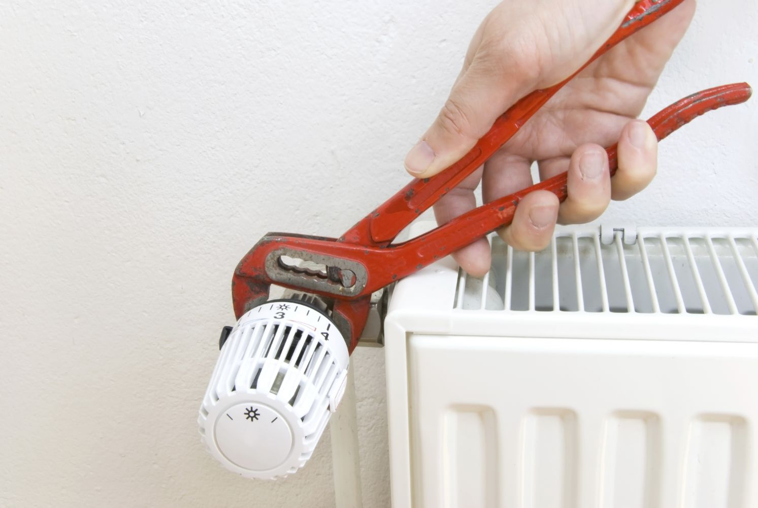heating contractors adjusting heater with a wrench in Wisconsin Rapids, WI