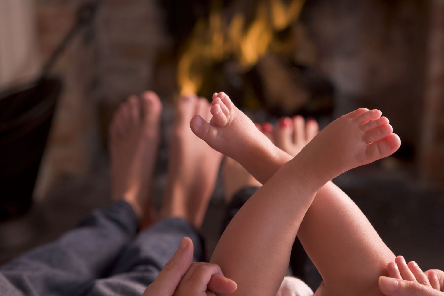 man and baby in front of fireplace installed by heating and cooling services in Wisconsin Rapids, WI