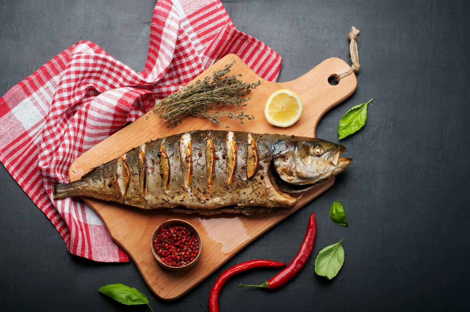 Un tagliere con un pesce grigliato e accanto degli aromi