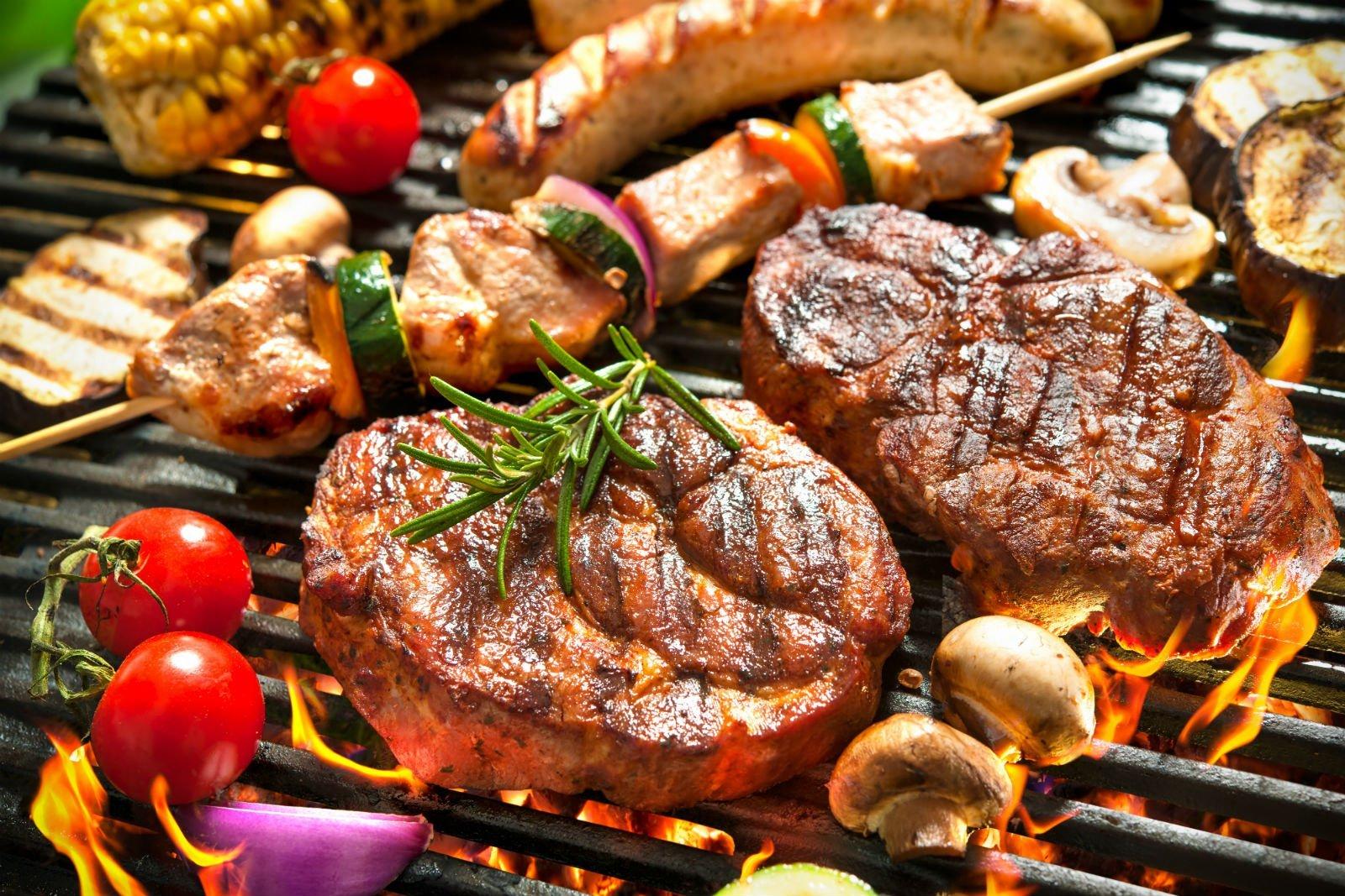 Degli spiedini e degli hamburger sulla griglia
