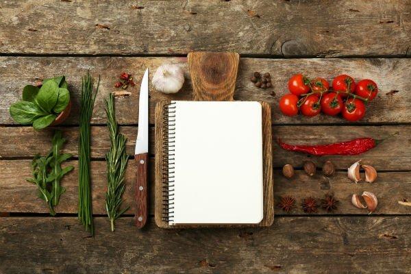Un tagliere con un quaderno, degli aromi e delle spezie