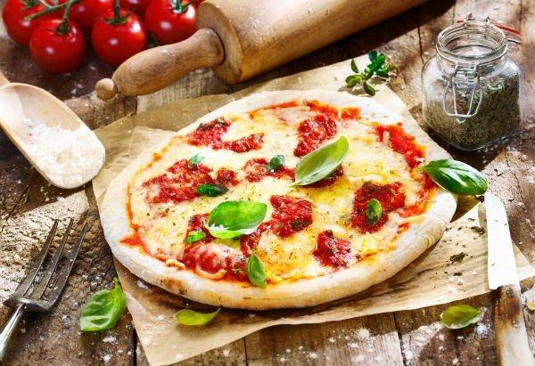 Una pizza e accanto un barattolo di aromi