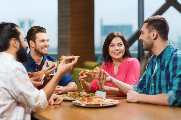 Una donna e tre uomini mentre mangiano una pizza
