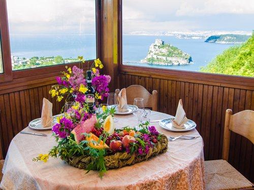 tavolo rotondo apparecchiato con vista sul mare
