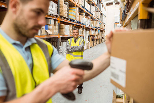 Warehouse worker scanning box with worker in back smiling with crossed arms in warehouse in Melbourne