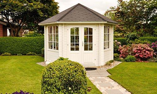 Bianco gazebo chiuso in giardino in estate