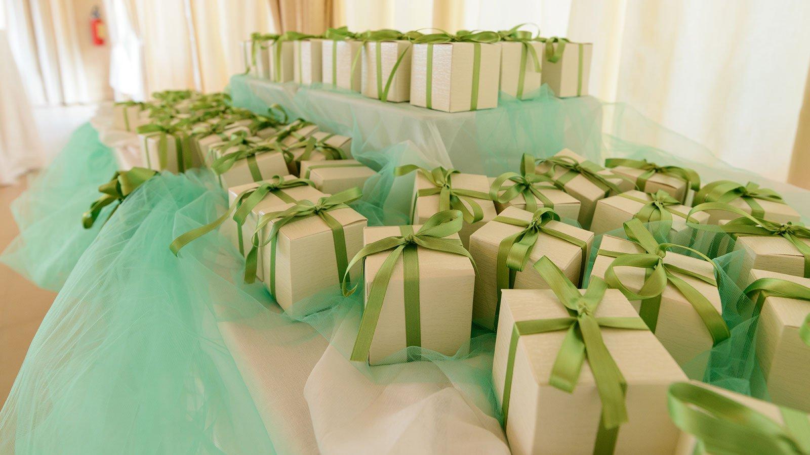 Delle bomboniere in pacchettini regalo con fiocchi verdi