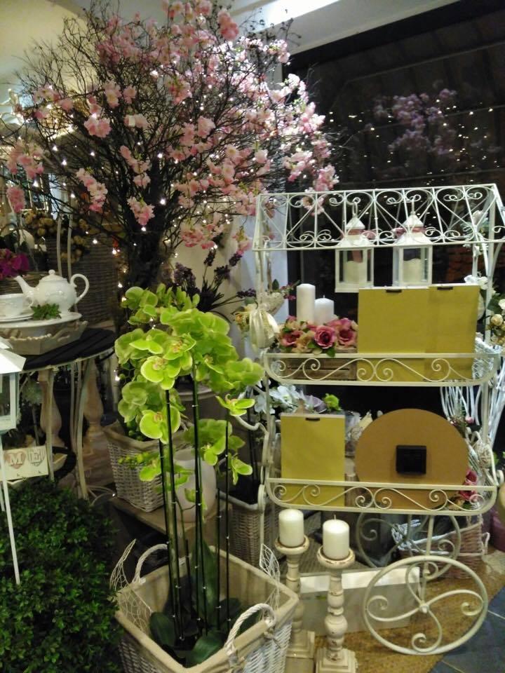 Uno scaffale in ferro battuto con oggetti e orchidee di color verde