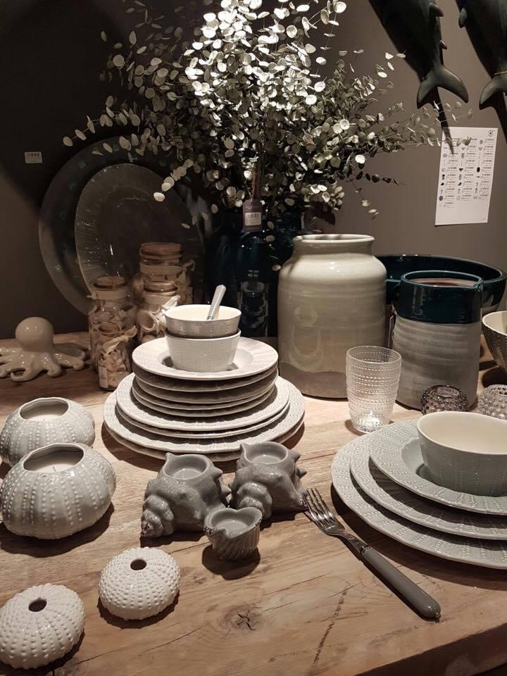 Un tavolo con dei piatti bianchi e dei portalumini