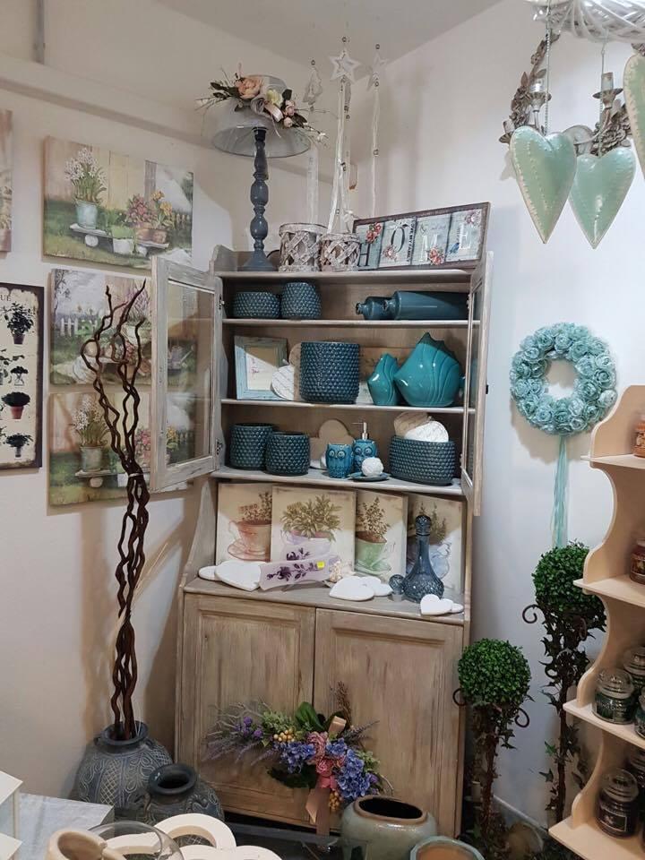 Un mobile in legno con dei vasi di color turchese e dei quadri con dipinti di fiori