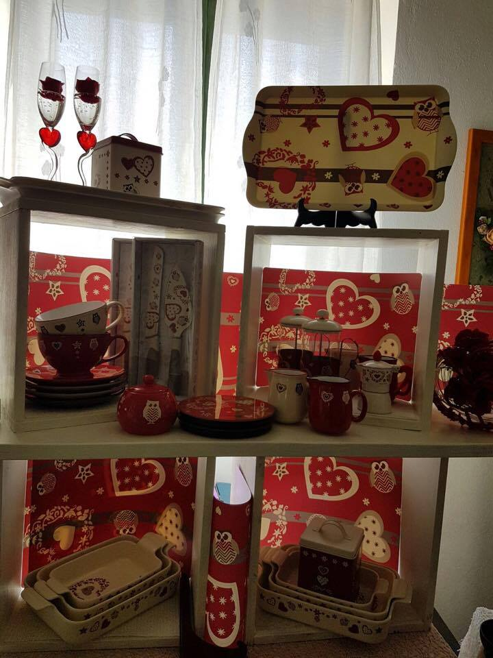 Delle tazze, bicchieri e vassoi di color bianco e rosso con disegni a forma di cuore