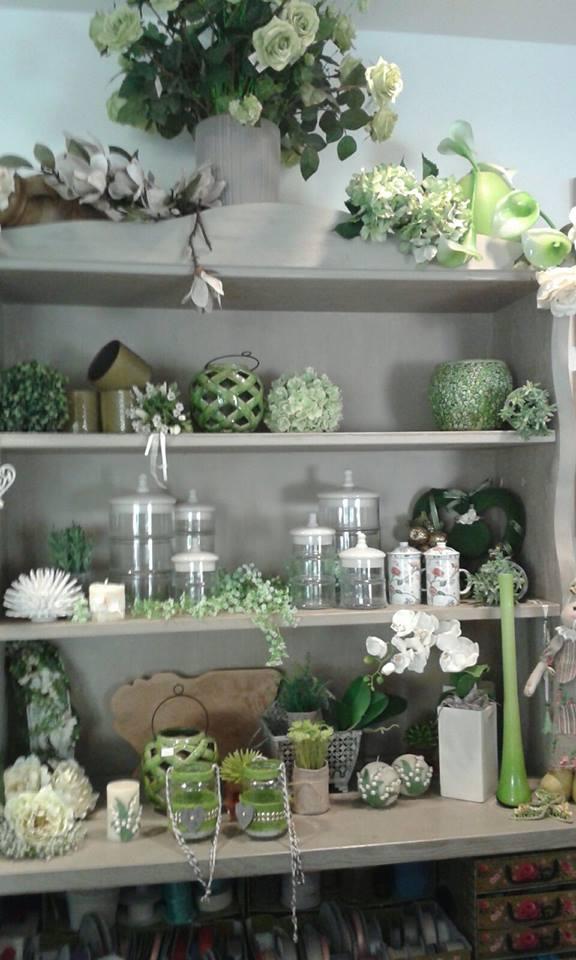 Dei vasi, barattoli e fiori di color verde e bianco