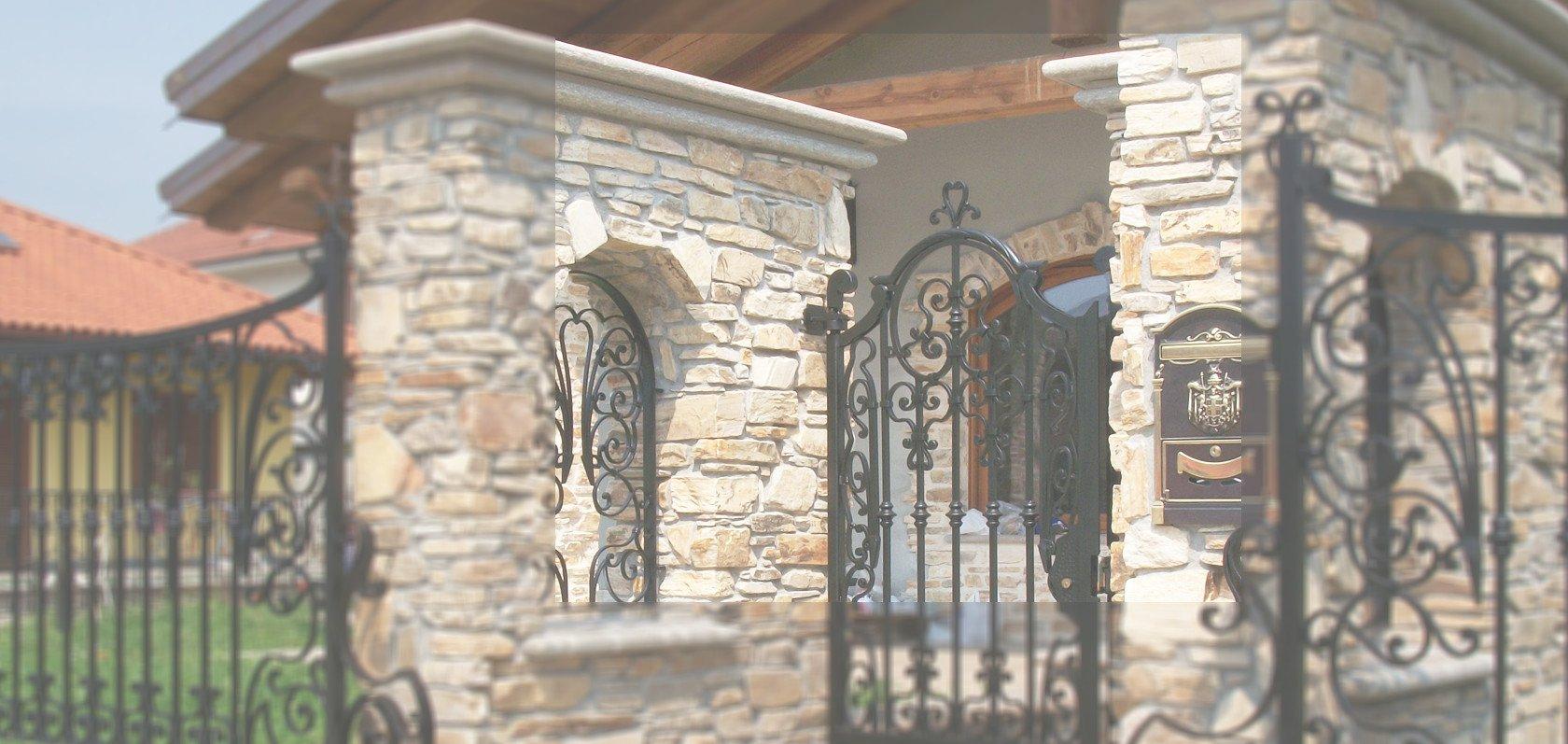 vista esterna di una casa con cancelli in ferro e parete in pietra