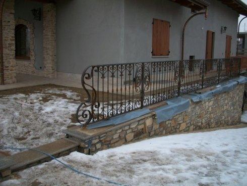 ringhiera in ferro con parete in pietra