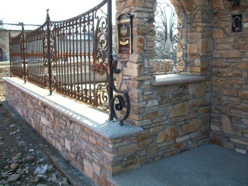 vista angolare di una casa con ringhiera in ferro e parete in pietra