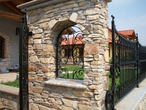 cancello in ferro aperto e parete in pietra