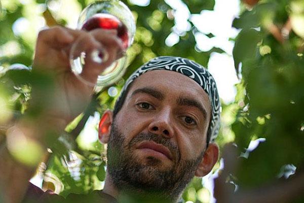 Un uomo in posa con un calice di vino rosso