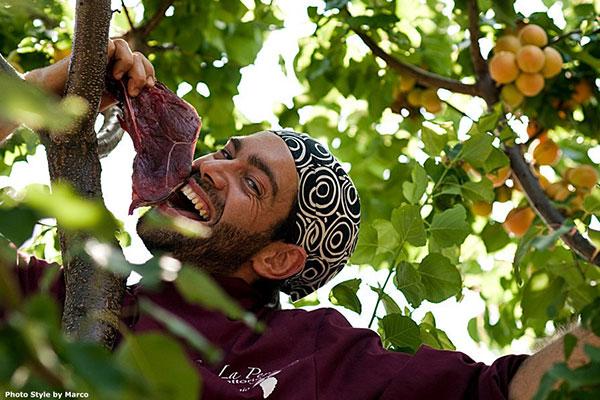 Un uomo con un  camice di color viola con una bistecca in mano tra gli alberi