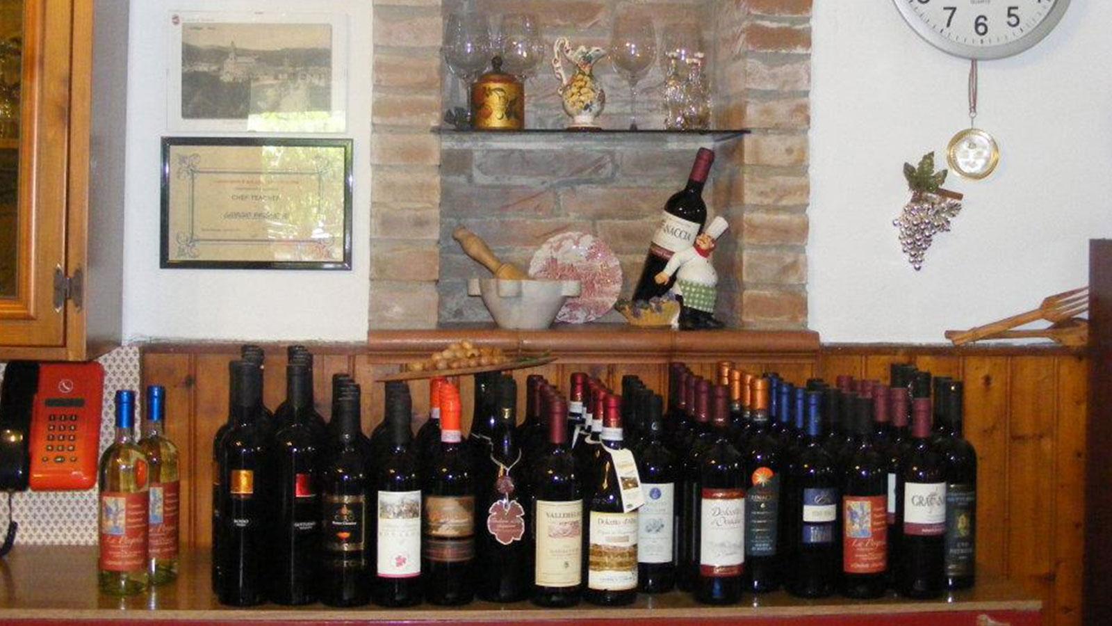 Una mensola di legno con varie bottiglie di vino esposte e alcune mensole, oggetti e bicchieri di vino
