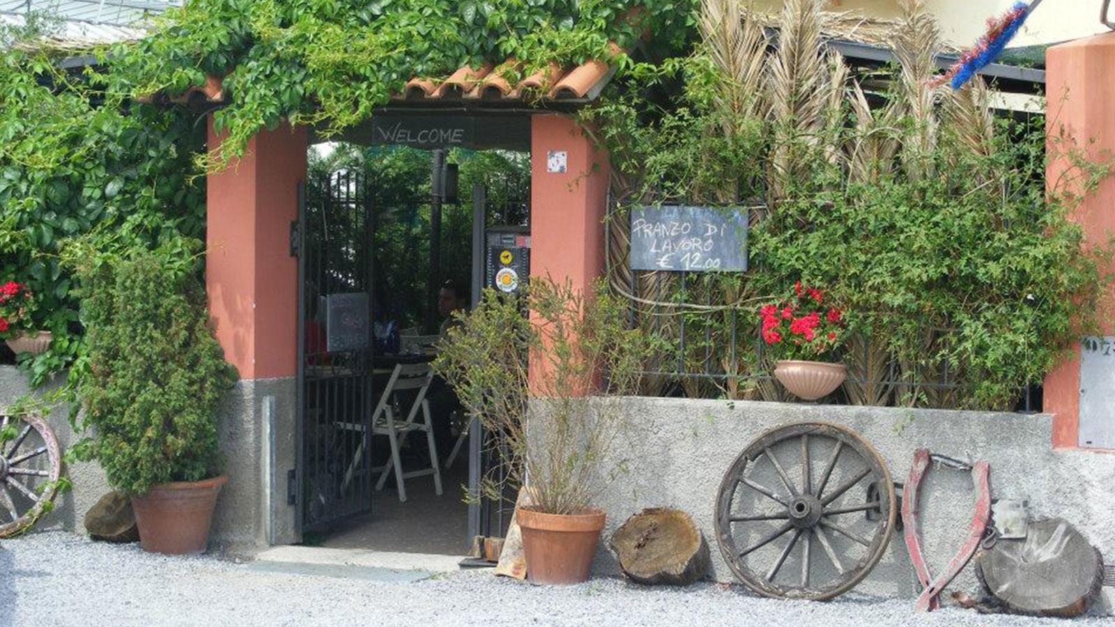 Vista dell'entrata di una trattoria con scritto Welcome e un cartello con scritto Pranzo di lavoro 12 euro