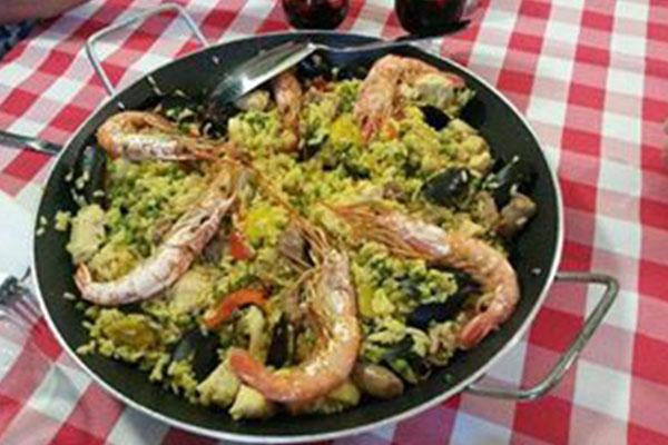 Una padella con paella e due caraffe con vino rosso appoggiato su una tavola