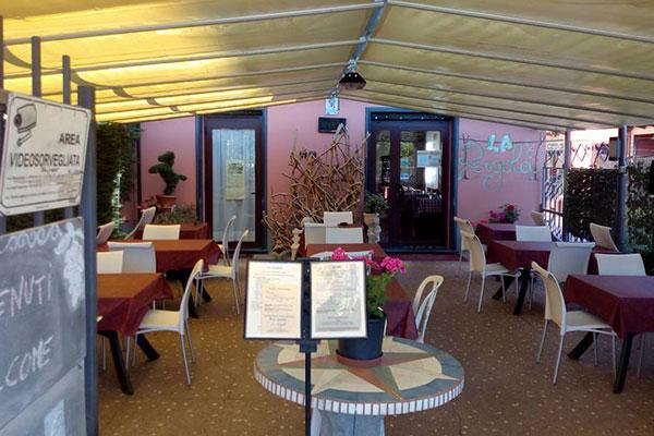Tavoli con delle tovaglie rosse all'esterno di un ristorante e un tavolino con un vaso di fiori