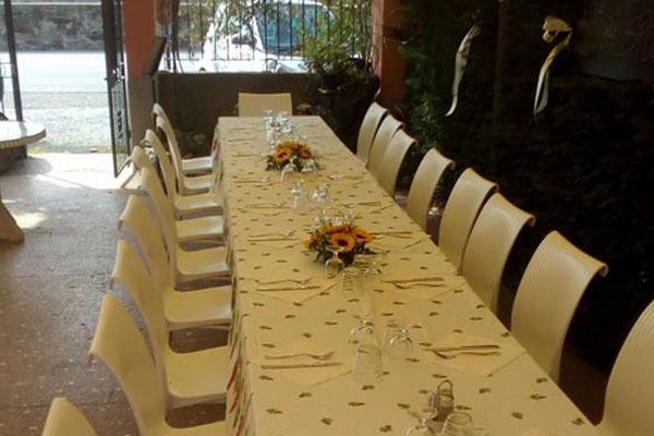 Una tavola lunga con un vaso di girasoli e bicchieri all'interno di un ristorante