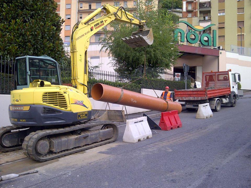 macchinario giallo che alza un tubo arancio