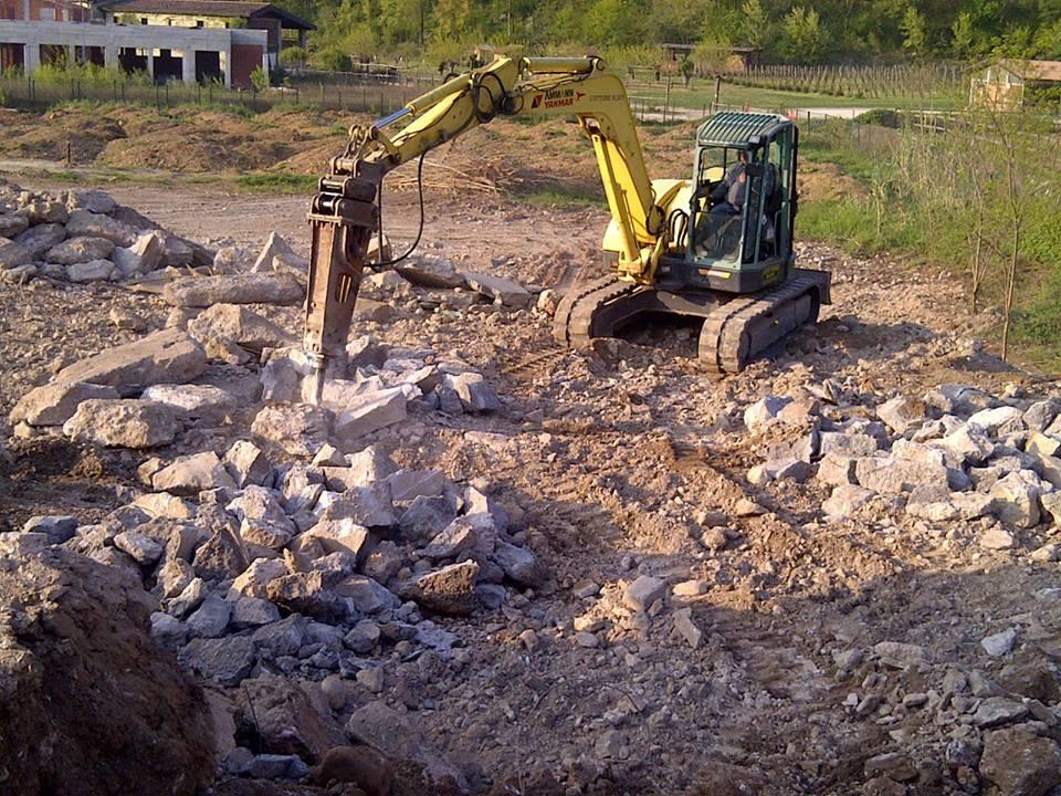 ruspa che scava e rompe dei mezzi di cemento
